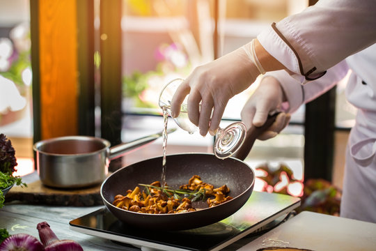 Liquid pours onto mushrooms. Hand holding glass over pan. Chanterelles fried in wine. Chef tries new recipe.