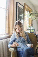 Young woman using mobile phone while holding coffee cup in cafe