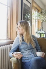 Thoughtful woman with mobile phone and coffee cup looking out through cafe window