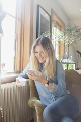 Happy woman using mobile phone while holding coffee cup in cafe