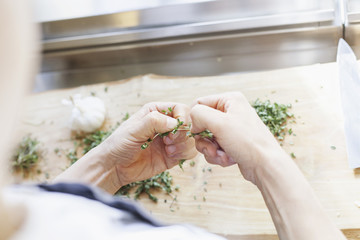 Cropped image of chef cleaning lemon thymes in kitchen