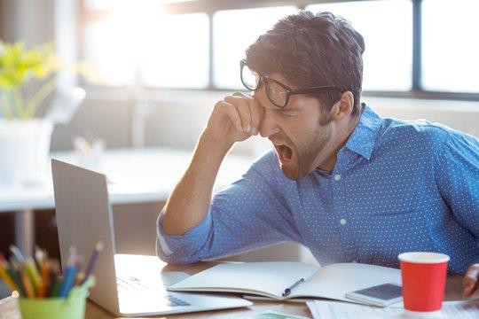 Male business executive yawning