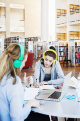Woman writing notes while wearing headphones connected to laptop in library