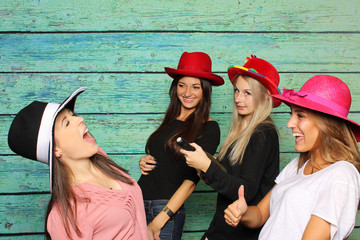 Fröhliche Mädchengruppe mit Damenhüte und Sekt - Fotobox Party mit Mädchengruppe