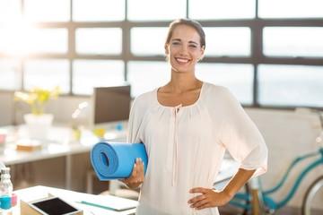 Female business executive holding exercise mat
