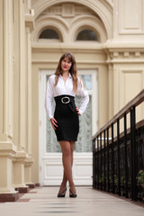 Beautiful brunette woman wearing white blouse and black skirt