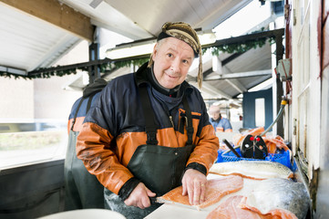 Happy mature fisherman filleting salmon in fishing industry