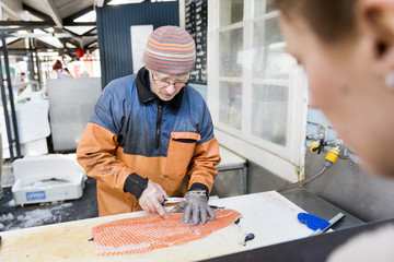 Young woman looking at mature fisherman cleaning salmon at fishing industry