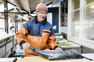 Mature man in protective workwear cleaning large fish in fishing industry