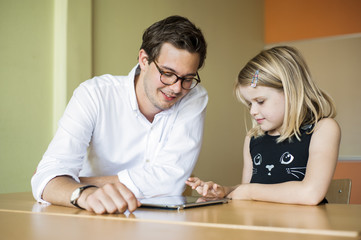 Father and daughter using tablet at table