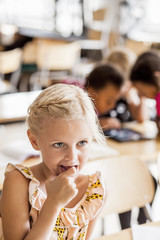 Girl with finger in mouth sitting at desk in classroom