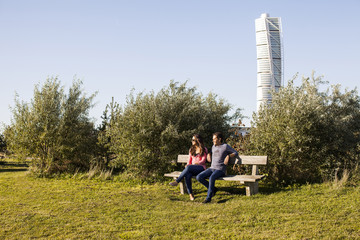 Young couple relaxing on park bench with Turning Torso skyscraper in background