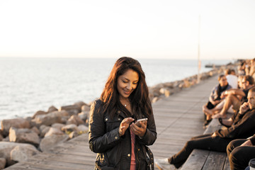 Smiling woman using mobile phone on boardwalk by sea against clear sky