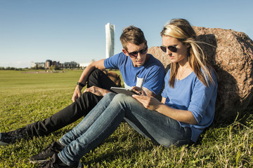 Woman and man sitting on lawn, using digital tablet