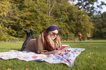 Full length of young woman reading book while lying on picnic blanket at forest