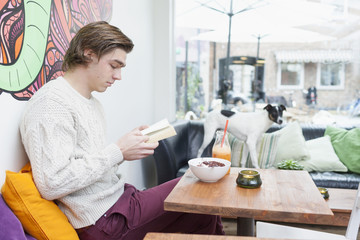 Young man reading book at cafe table with dog on sofa in background