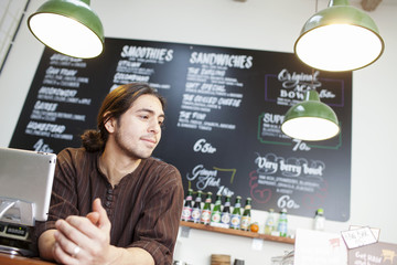 Thoughtful male owner looking away while leaning at cafe counter