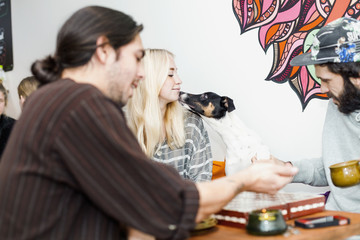 Loving dog touching woman's chin while friends playing board game at cafe table