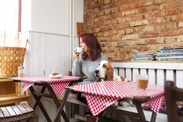 Young Woman Drinking Coffee With Basset Hound Sitting At Cafe Table