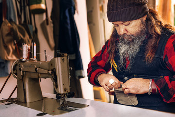 Worker checking pocket of bag at sewing table in workshop