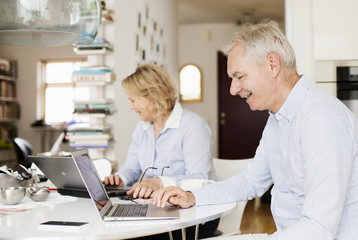 Happy senior business couple using laptops at home