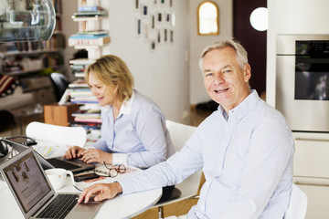 Portrait of happy senior man with woman using laptops at home