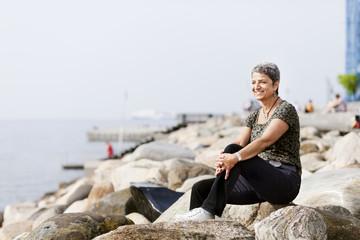 Full length of happy mature woman relaxing on rocks at seashore