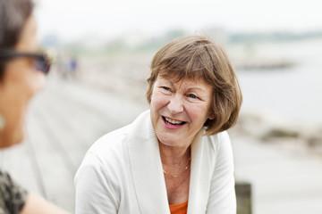 Happy senior woman talking with female friend at seashore