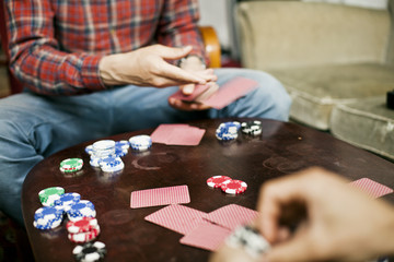 Cropped image of men playing cards at home