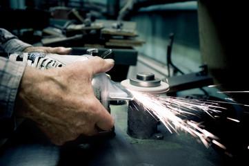 Cropped image of worker sharpens the blades on skate in workshop