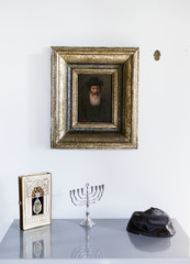 Picture frame above menorah, holy book and cap on table