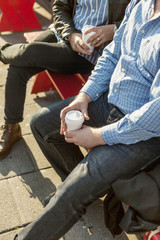 Cropped image of businessmen holding disposable cups while sitting on bench outdoors
