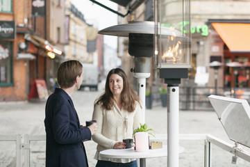 Happy friends having coffee at sidewalk cafe in city