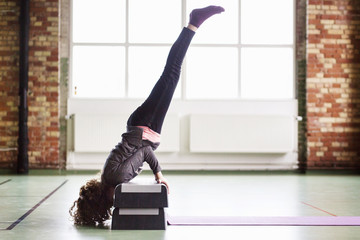Full length side view of female dancer doing handstand on steps