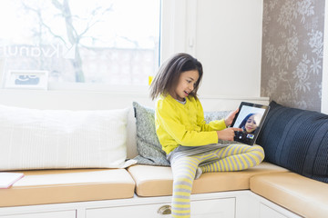 Little girl looking at her photograph on digital tablet in living room