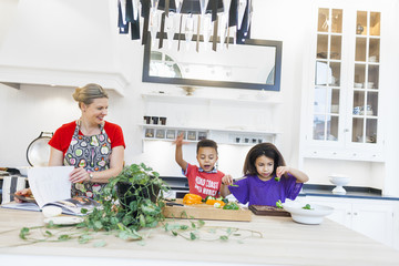 Mother with children cooking together in kitchen