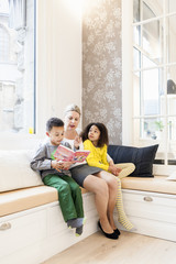 Full length of children listening mother reading story book in living room