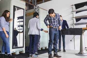 Woman looking at man trying jeans in factory