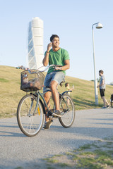Handsome young man using mobile phone riding bicycle in city