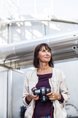 Woman holding digital camera outside building