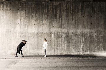 Woman photographing friend on sidewalk against wall
