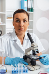Woman working with a microscope in a lab.