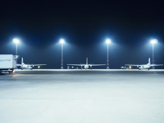 Illuminated floodlights in front of airplanes parked at terminal