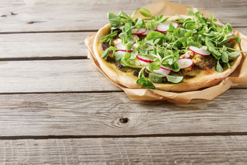 Home Italian pizza with pesto, lettuce and radish on baking pape