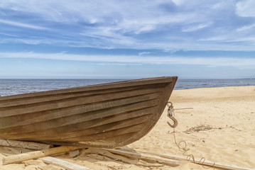 Old wooden fishing boat on beach. Blue sky with white clouds. Sunny day