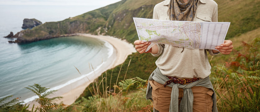 woman hiker looking at map in front of ocean view landscape