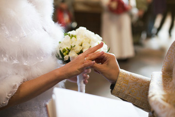 Priest puts a wedding ring on a bride's hands during the ceremon