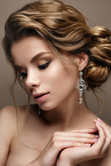 Beautiful girl in the image of a bride with bright earrings. Model with a gentle makeup in beige tones. Beauty face. Photo is taken in a studio.