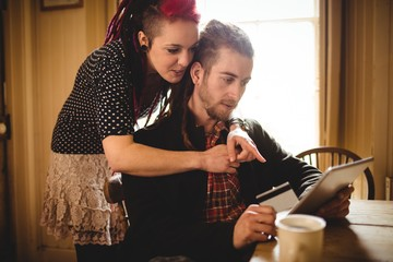 Hipster couple using tablet for online shopping