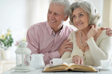 Senior couple drinking tea  with book